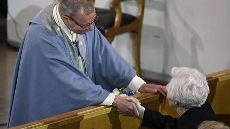 Emerituspiispa Eero Huovinen kätteli rouva Tellervo Koivistoa Mauno Koiviston siunaustilauksen aluksi.
