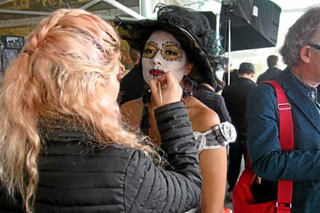 Elokuvan 1500 extranäyttelijää saavat meksikolaiseen kuolleiden päivän juhlaan sopivan meikin. Meikkiassistentti Samanta Rodriguez kohentaa Montserrat Ambrosio Lopezin meikkiä kuvaustauolla.