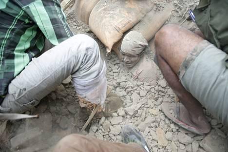 Ihmiset yrittävät auttaa järistyksen jäljiltä hautautuneita ihmisiä.