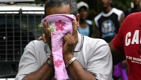 Epäilty peitti kasvonsa, kun häntä kuljetettiin oikeuteen Port Louisissa, Mauritiuksella.