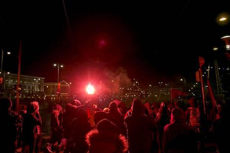 Anarkistit polttivat punaisia soihtuja Lähiöstä linnaan -marssilla.