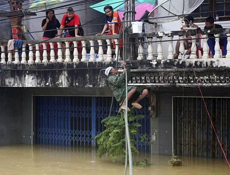 Mies kiipeää narua pitkin turvaan tulvien piinamassa Nakon Si Thammaratin maakunnassa.