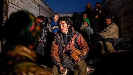 Kurdijoukoille antautuneita Isis-taistelijoita ja heidän mukanaan tulleita naisia ja lapsia Baghouzin kylän edustalla Syyriassa maanantaina.