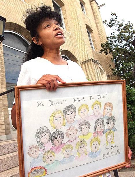 Lahkolainen Sheila Martin vuonna 2000. Hän piteli taulua, jossa oli tulipalossa kuolleiden lasten kuvia.