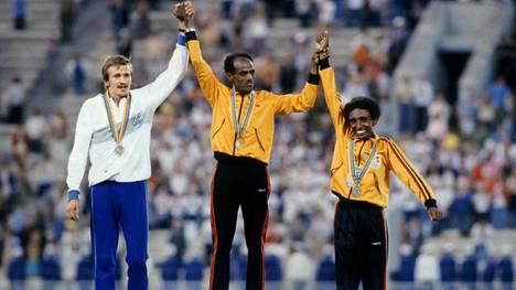 Etiopian Miruts Yifter (keskellä) juhli voittoa 10 000 metrin olympiafinaalin palkintojenjaossa. Hänen vasemmalla puolellaan hopealle sijoittunut Suomen Kaarlo Maaninka ja oikealla Etiopian pronssille sijoittunut Mohammed Kedir.
