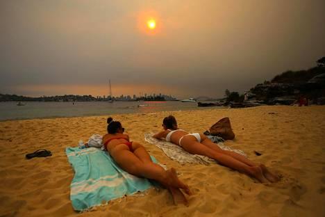 Ihmiset makoilivat rannalla Sydneyssä synkästä savusta huolimatta.