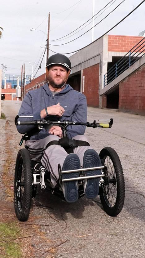 Janne Kouri testaa maastopyörätuoliaan kuntosalin takana.