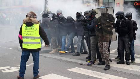 Keltaiseen liivin pukeutunut mielenosoittaja ja poliiseja Pariisissa 2. helmikuuta 2019.