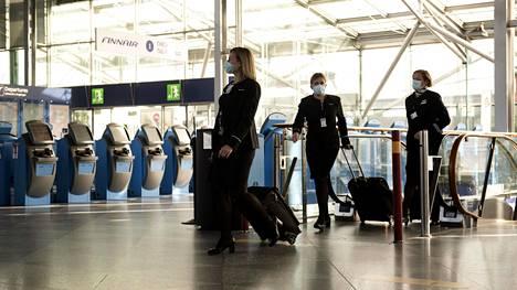 Finnairin henkilökuntaa menossa turvatarkastukseen Helsinki-Vantaalla tiistai-iltana.
