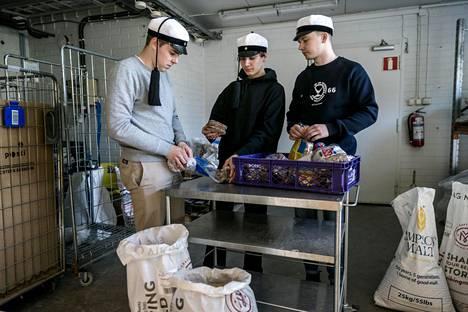 Aalto-yliopiston opiskelijat Mikael Nuotio, Jusa Annevirta ja Joel Knorn käyvät läpi panimolle tuotuja leipiä. Vastaavia hävikkileipiä käytetään oluen raaka-aineena.