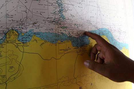 Pelastuspartion jäsen osoittaa paikkaa, josta turmakonetta etsitään.