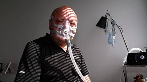 Tapio Suominen esittelee uniapnean hoitoon tarkoitettua maskia kotonaan.