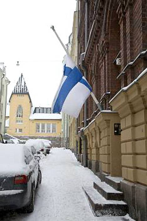 Kirkan kotitalon ovella on lippu puolitangossa.