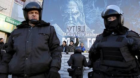 Ukrainalaispoliisit seisoivat mieltään osoittavien hallituksen vastustajien ja puolustajien välissä lauantaina.