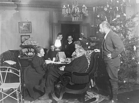 Zacharias Topelius perheensä kanssa Koivuniemen salissa jouluna 1897. Vasemmalla Aline Haeggström, pöydän takana Paul Nyberg, Alta Dahlgren ja Zachris Nyberg. Topeliuksen tytär Toini isänsä takana. Eva-tyttären puoliso Johan Axel Gustaf Acke seisoo appensa kiikkutuolin takana.