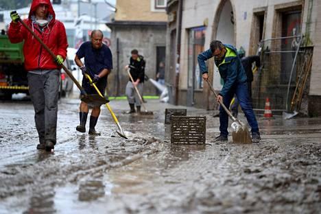 Miehet siivosivat mutaa Halleinin kaupungissa sunnuntaina.