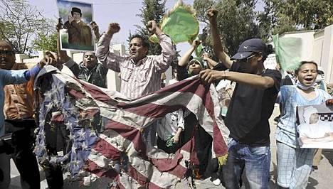 Muammar Gaddafin hallinnon kannattajat polttivat Yhdysvaltain lipun rakennuksen ulkopuolella, jossa Gaddafin nuorin poika sai surmansa Naton ilmaiskussa.