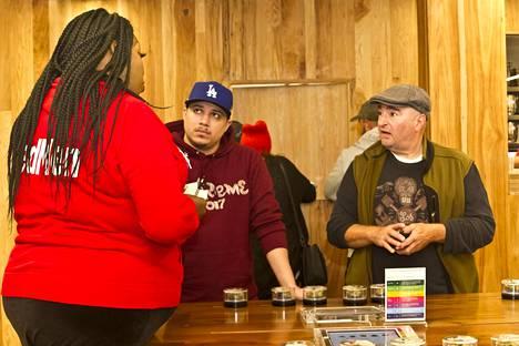 West Hollywoodin MedMen -liikkeen asiakkaita ja punapukuisia työntekijöitä. Liike täyttyi asiakkaista marihuanan viihdekäytön tultua lailliseksi Kaliforniassa.