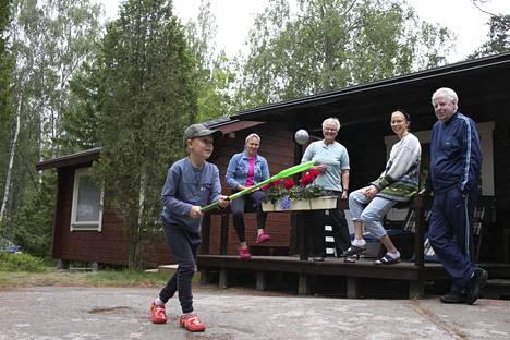 Kolme sukupolvea viihtyy yhdessä kesämökillä. Tuua (vas.), Anneli ja Pekka Uskali sekä Annika Varpe (2. oik.) seuraavat Jooa Uskalin salibandytreenejä.