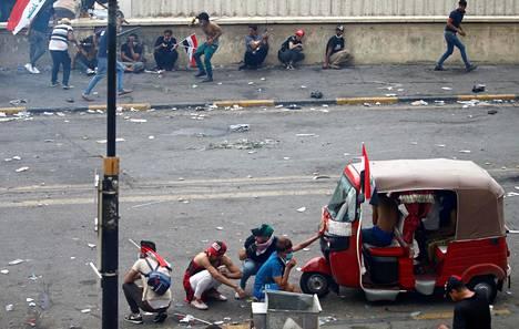 Mielenosoittajat suojautuvat Bagdadissa Irakissa.