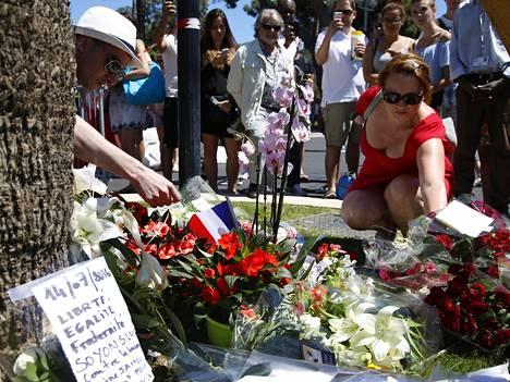 Ihmiset laskivat kukkia lähelle paikkaa, jossa yli 80 ihmistä kuoli terrori-iskussa Nizzassa myöhään torstai-iltana.
