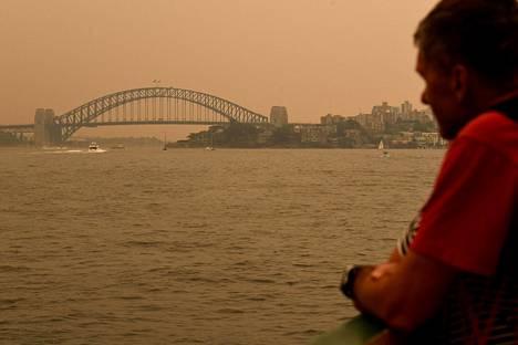 Mies katseli savun peittämää Sydneyn kaupunkia perjantaina.