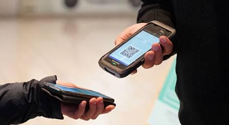 Latviassa ihmisillä on puhelimessa koronapassin QR-koodi.