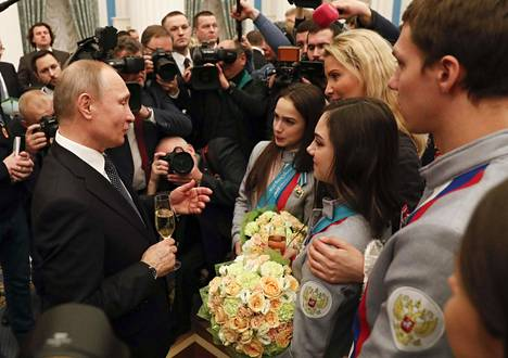 Putin hymyili maireana venäläisten taitoluistelutähtien Alina Zagitovan (vas.) ja Jevgenia Medvedevan seurassa. Zagitova voitti Etelä-Koreassa olympiakultaa, viimeisimmät vuodet naisten yksinluistelua hallinnut Medvedeva otti hopeaa.
