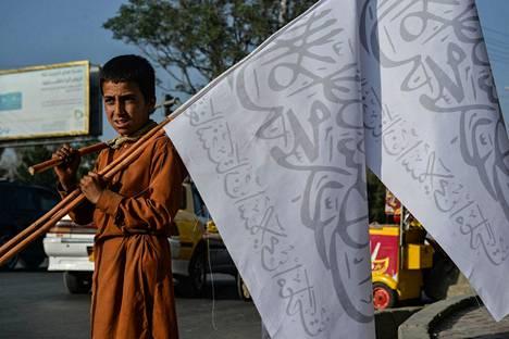 Poika myy Talebanin lippuja Kabulissa.