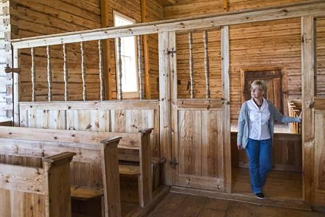 Anne Wilenius seisoo ovella, joka erotti spitaaliset ja terveet kirkossakävijät erillisiin penkkeihin.
