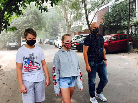 Eino ja Mimmi isänsä Jukan kanssa saastesuojaimet kasvoillaan.