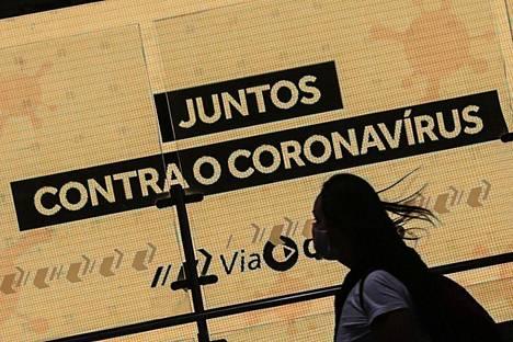 """Nainen kävelee """"Yhdessä koronavirusta vastaan"""" -kyltin ohi Sao Paulossa 20. toukokuuta 2020."""