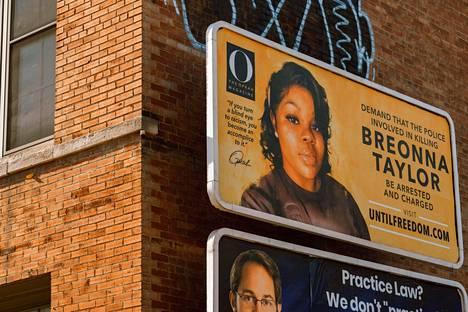 Kuva Breonna Taylorista. Kyltissä vaaditaan ampumisvälikohtauksessa mukana olleiden poliisien pidättämistä.