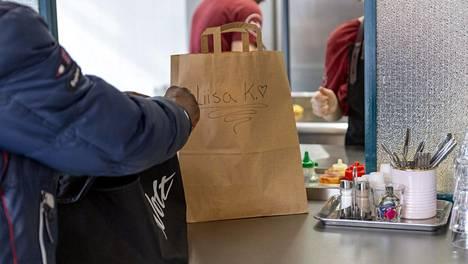 Wolt ruokalähetti noutaa annosta Bun2Bun -hampurilaisravintolasta Vaasankadulta Helsingissä 30. maaliskuuta 2020.
