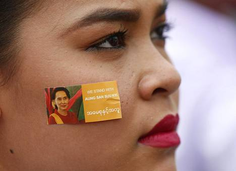 Nuori nainen kertoi kantansa poskitarralla mielenosoituksessa Rangoonissa.