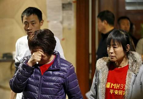 Kadonneella Malaysia Airlinesin lennolla MH370 olleiden matkustajien omaisia poistumassa keskiviikkona Malesian viranomaisten järjestämästä tiedotustilaisuudesta.