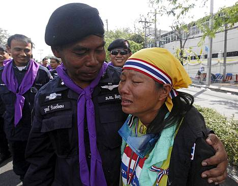 Mellakkapoliisi ja mielenosoittaja halailivat poliisin päämajan edustalla.