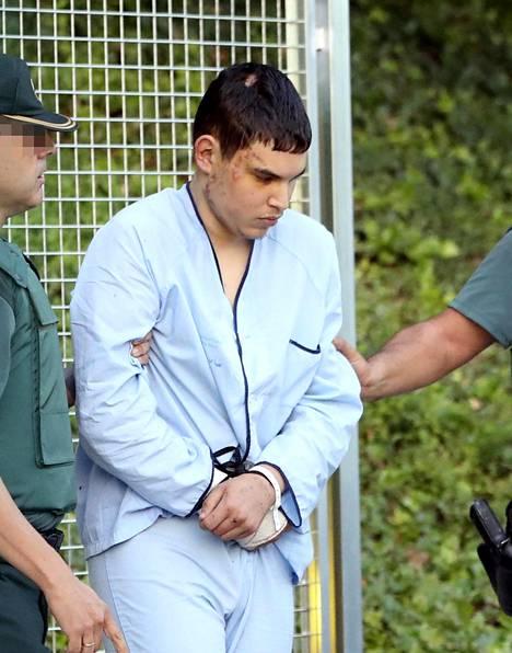 Espanjan iskuista epäilty Mohamed Houli Chemlal matkalla oikeuteen.