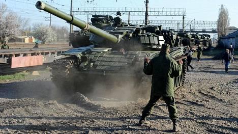 Venäläissotilaat purkavat T-72-panssarivaunujen junakuljetusta Gvardeiskojen asemalla lähellä Krimin pääkaupunkia Simferopolia maaliskuussa 2014. Krimin valtauksen jälkeen Venäjä on varustanut niemimaata voimakkaasti.