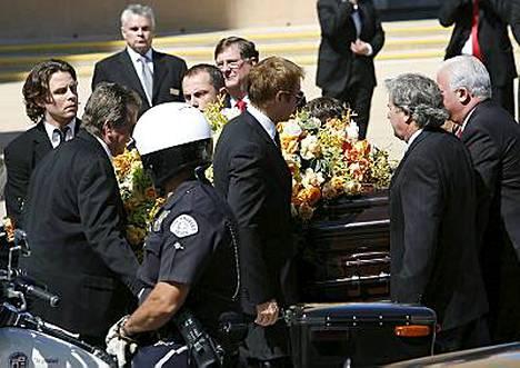 Farrah Fawcettin arkkua kannetaan haudan lepoon. Hänen kumppaninsa Ryan ONeal kuvassa vasemmalla.