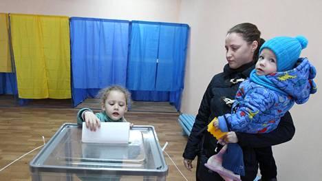 Pikkutyttö sai pudottaa äitinsä äänestyslapun Kiovassa sunnuntaiaamuna, kun presidentinvaalien ensimmäisen kierroksen äänestys oli alkanut.