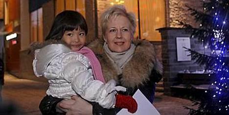 Leonoora, 5, poseeraa tottuneesti äitinsä liikenneministeri Suvi Lindénin sylissä.