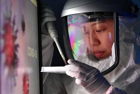 Eteläkorealaisen laboratorion työntekijä tekee covid-19-tautiin liittyvää lääketutkimusta.