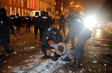 Poliisit ottavat kiinni mielenosoittajan.