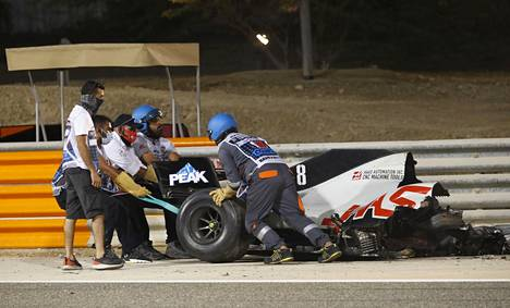 Henkilökunta siirtämässä osaa Grosjeanin autosta.