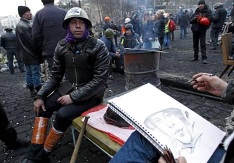 Mielenosoittaja poseerasi muotokuvapiirtäjälle Kiovan Itsenäisyyden aukiolla.