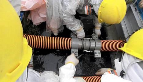 Tokion sähköyhtiön Tepcon työntekijät tutkivat putkiliitosta voimala-alueella lokakuun alkupuolella.