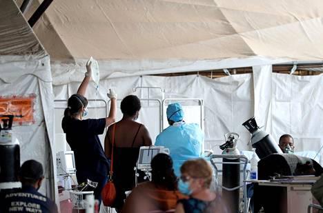 Hoitaja työskentelee koronaviruspotilaiden parissa sairaalan parkkipaikalle pystytetyssä teltassa Pretoriassa Etelä-Afrikassa. Etelä-Afrikasta lähtenyt koronavirusmuunnos saattaa olla osittain vastustuskykyinen kantaviruksen muodostamille vasta-aineille.