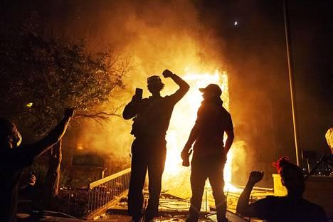 Mielenosoittajia palavan poliisiauton edessä Minneapolisissa, josta mellakat ja mielenosoitukset saivat alkunsa.