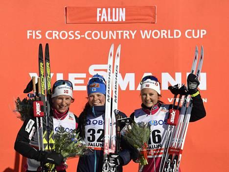 Marit Björgen, Krista Pärmäkoski ja Ingvild Flugstad Östberg juhlivat palkintopallilla Falunin auringonpaisteessa.